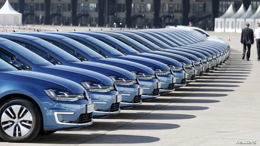 People walk past a row of Volkswagen e-Golf cars during the company's annual news conference in Berlin March 13, 2014.
