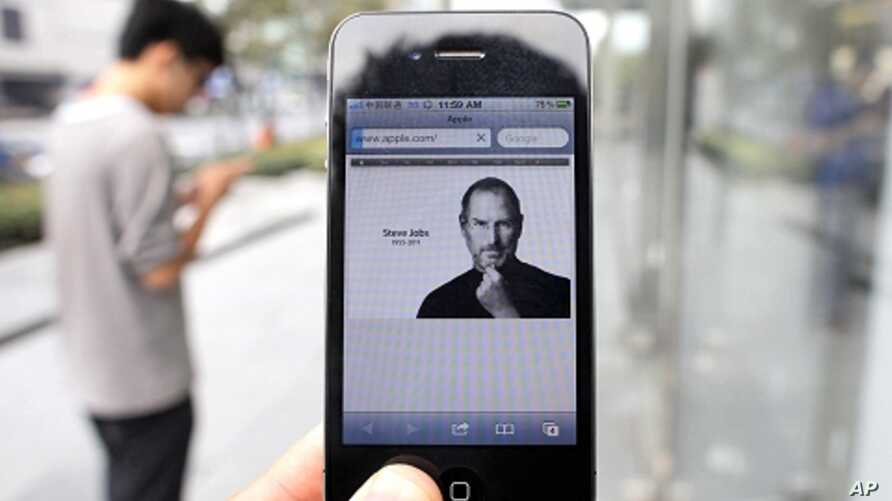 A man holds an iPhone 4 displaying an obituary of Apple co-founder Steve Jobs outside an Apple Store in downtown Shanghai October 6, 2011.