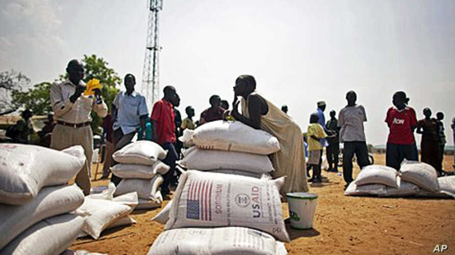 Southern Sudanese who recently returned from northern Sudan receive food rations from the World Food Program in the southern capital of Juba, 07 Jan 2011