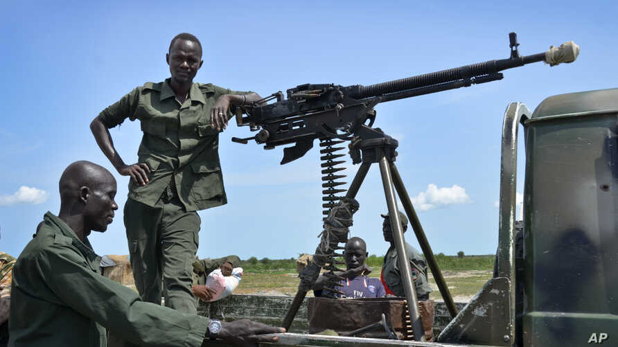 FILE - Government soldiers stand guard by their vehicle on the front lines in the town of Kuek, northern Upper Nile state, South Sudan, Aug. 19, 2017