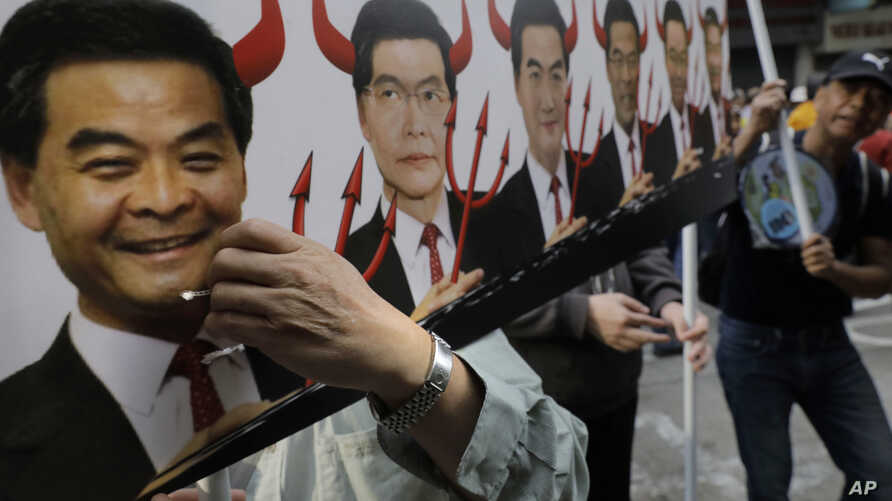 A protester raises a poster depicting outgoing Chief Executive Leung Chun-ying, left, with devil horns during a rally on the first day of 2017 in Hong Kong, Jan. 1, 2017.