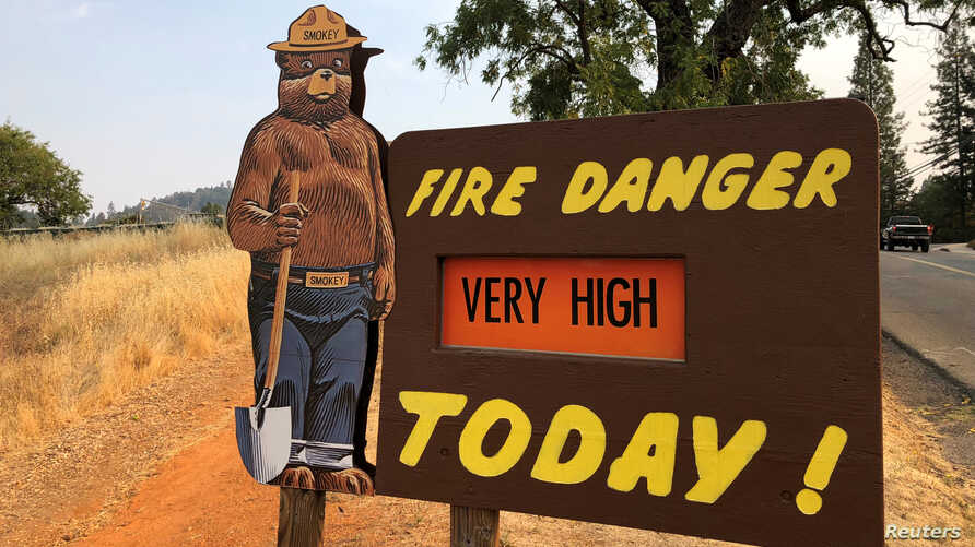 A sign by the side of the road warns of the threat of wildfires, which have been fueled by continued hot weather, outside the town of Colfax, Calif., Aug. 4, 2018.