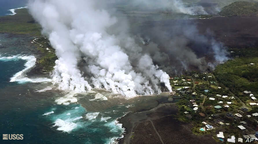 The photo, provided by the U.S. Geological Survey, June 4, 2018, shows lava from a fissure flowing into the ocean at Kapoho Bay at Kapoho on the island of Hawaii. After overrunning the town overnight and destroying hundreds of homes, the lava flowed