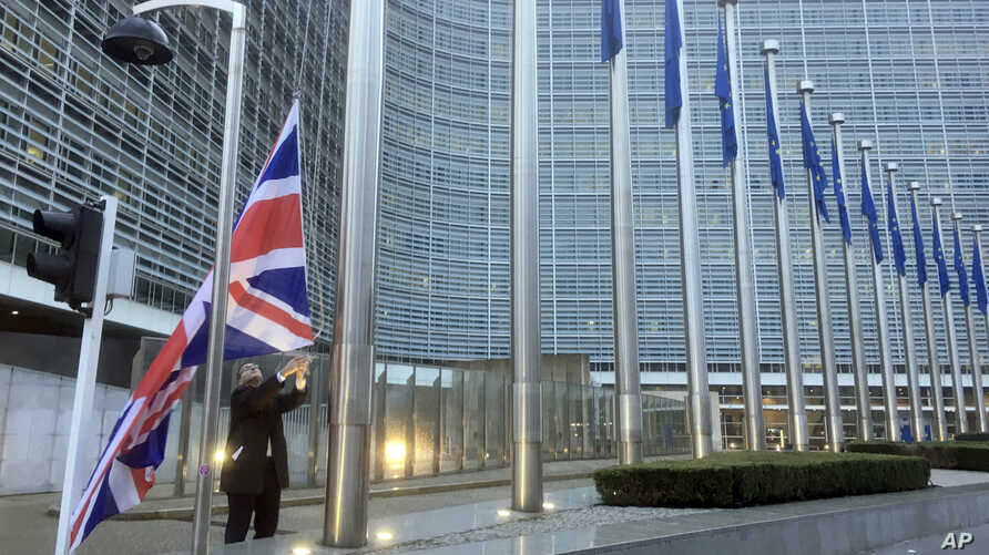 FILE - A member of protocol hoists the British flag outside EU headquarters in Brussels, Belgium, Dec. 4, 2017.