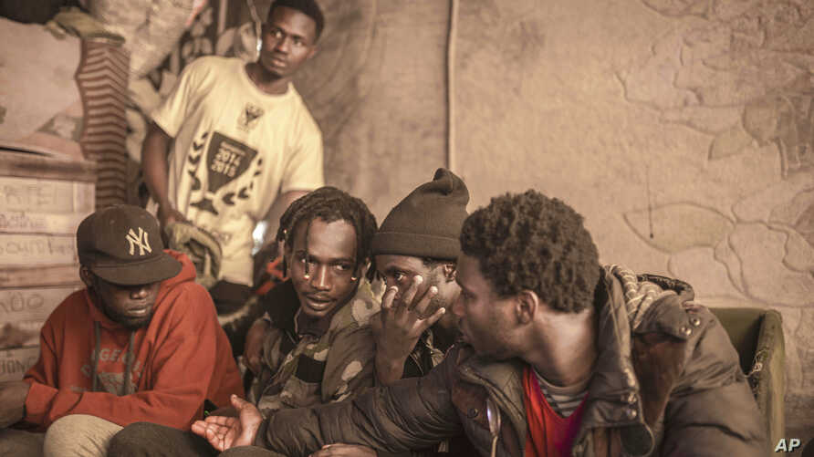 Sub-Saharan migrants sit in a tent they share at Ouled Ziane camp in Casablanca, Morocco, Dec. 6, 2018.