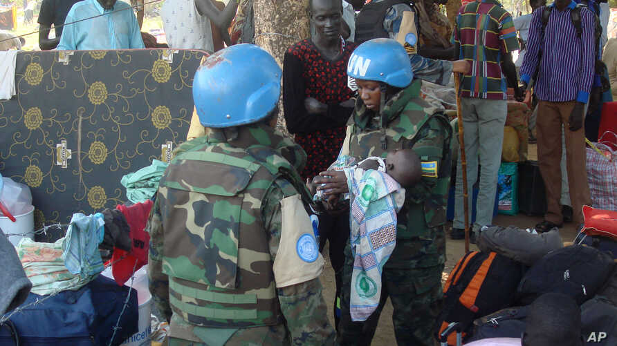 In this photo taken Thursday, July 14, 2016 and released by the United Nations Mission in South Sudan (UNMISS), UN peacekeeper soldiers hold a baby as South Sudanese people seek protection at the UN camp in Juba, South Sudan