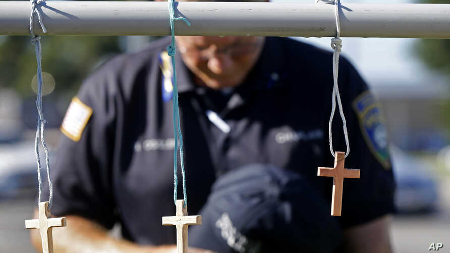 A police chaplain pays his respects July 18, 2016, at a makeshift memorial at the fatal shooting scene in Baton Rouge, Louisiana, where three law enforcement officers were ambushed and killed by a lone gunman on Sunday.
