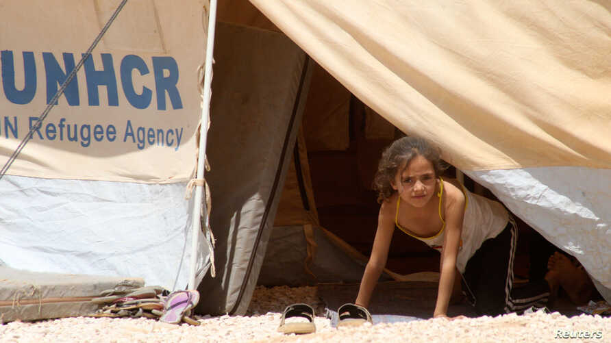 A Syrian refugee girl looks out from a tent amidst dust at Al Zaatri refugee camp in the Jordanian city of Mafraq, near the border with Syria, August 13, 2012.