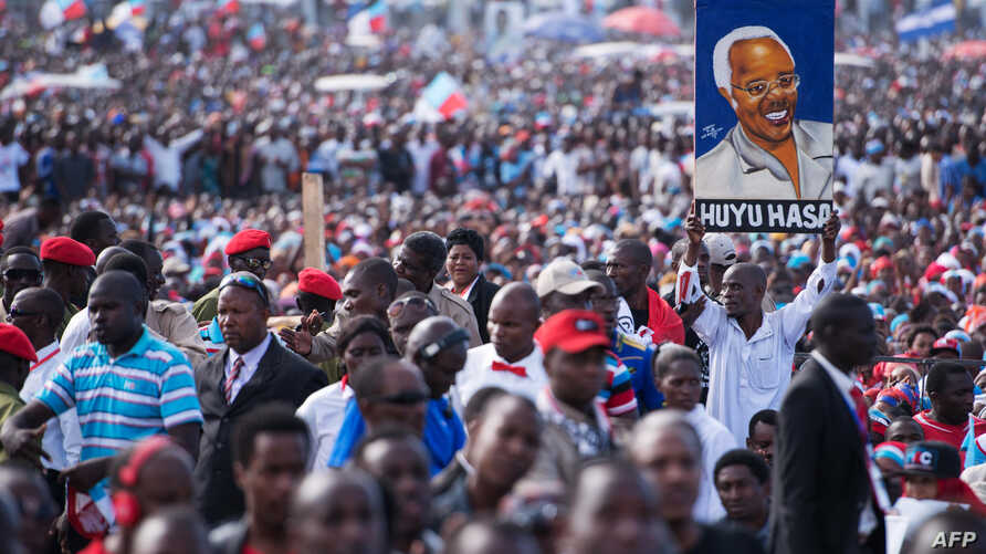 A man holds up a painted portrait of Edward Lowassa, former prime minister of Tanzania and presidential candidate for UKAWA, a coalition of four main opposition parties, during a political rally in Dar es Salaam, Tanzania, Aug. 29, 2015.