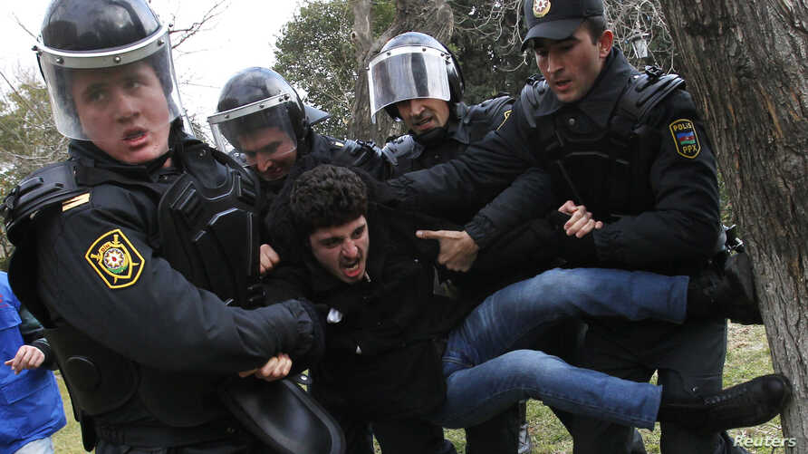 """FILE - Police officers detain a man during a rally in Baku, Azerbaijan, Jan. 26, 2013. In addition to arresting 20 political and youth activists in 2016 on """"spurious charges,"""" the Azeri government has severely limited the ability of independent group"""
