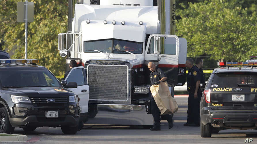 San Antonio police officers investigate the scene where eight people were found dead in a tractor-trailer loaded with at least 30 others outside a Walmart store in stifling summer heat in what police are calling a horrific human trafficking case, Sun
