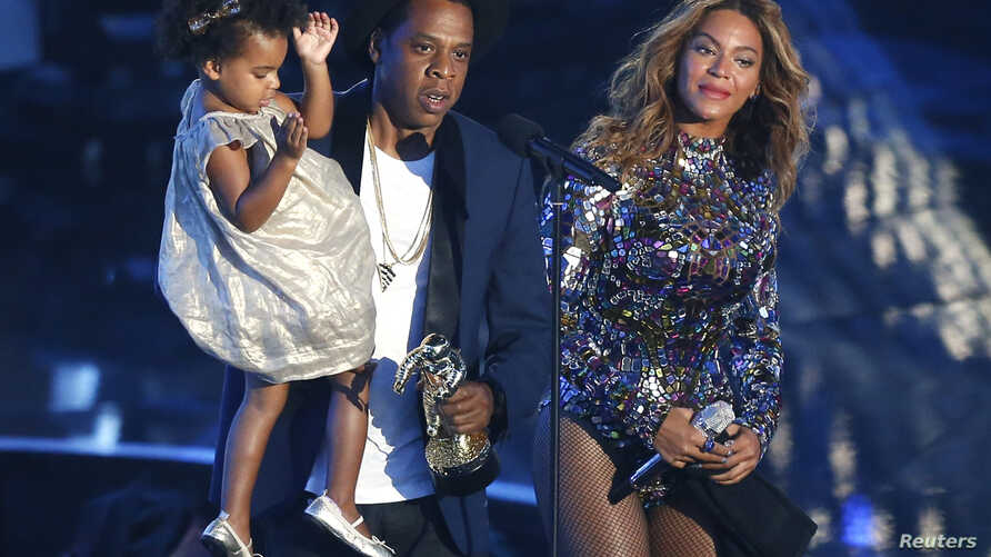 Jay-Z presents the Video Vanguard Award to Beyonce as he holds their daughter Blue Ivy during the 2014 MTV Video Music Awards in Inglewood, California Aug. 24, 2014.