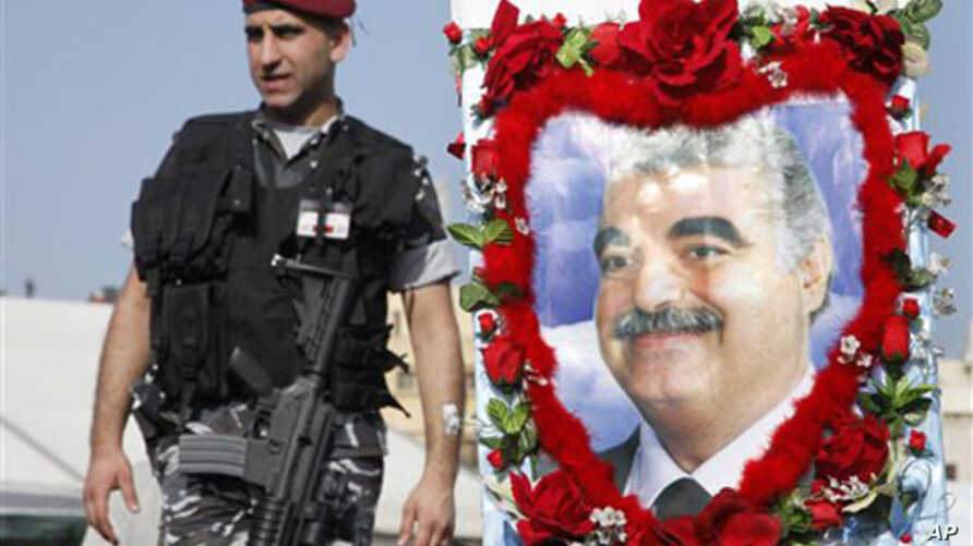 A Lebanese police stands guard near a decorated picture of slain former Prime Minister Rafiq Hariri during a rally in Beirut's Martyrs' Square, Lebanon, 14 Feb 2010.