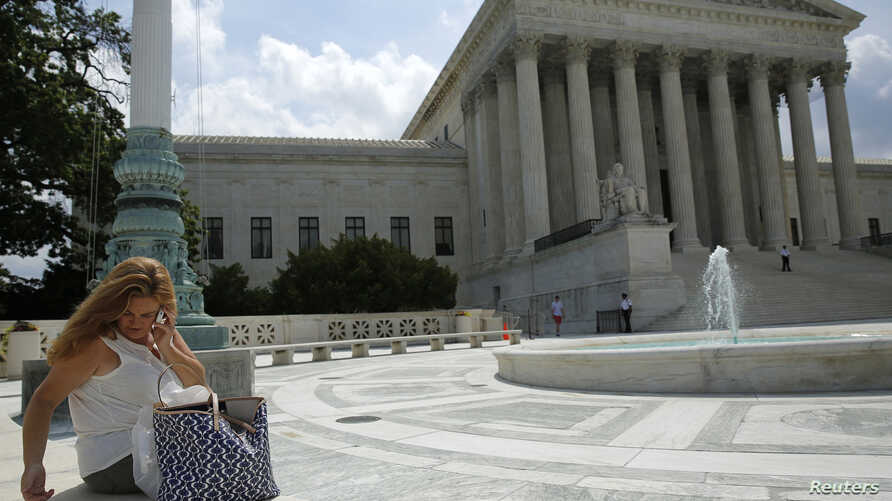 A woman uses her mobile phone at the plaza of the U.S. Supreme Court, Washington, June 25, 2014.