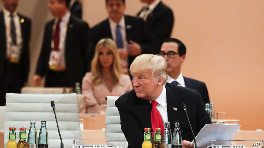 U.S. President Donald Trump sits in front of his delegation with daughter Ivanka Trump, background center, as he attends a working session at the G-20 summit in Hamburg, northern Germany, July 8, 2017. T