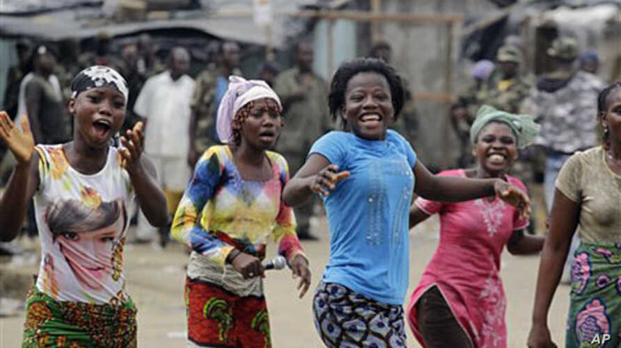 Local residents react to news of the capture of Laurent Gbagbo in the Youpougon neighborhood of Abidjan, Apr 11 2011