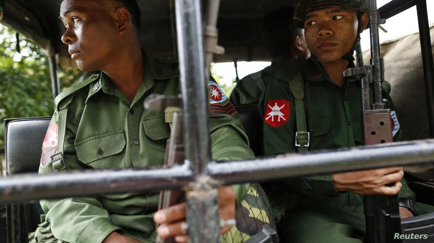 FILE - Soldiers keep watch as they sit in a vehicle outside of Thandwe in Rakhine state Oct. 3, 2013.
