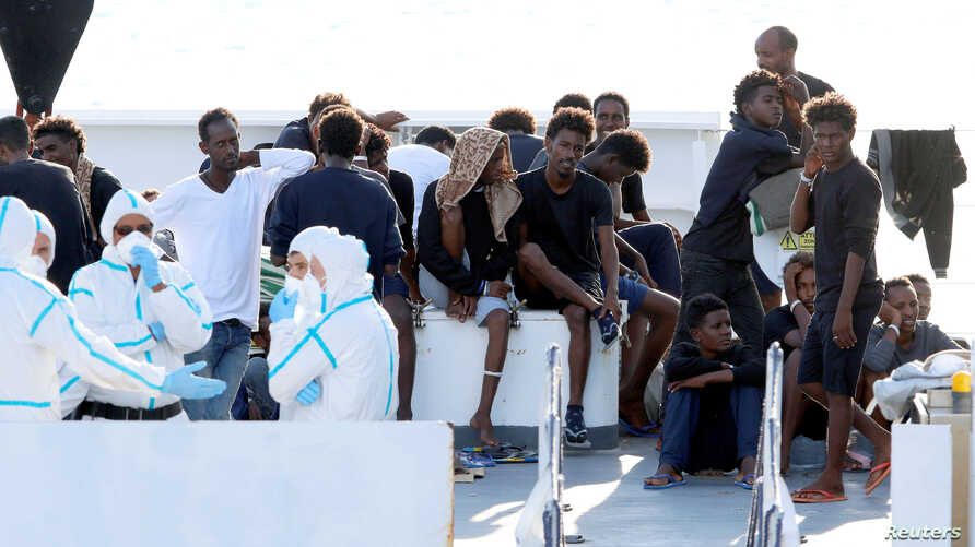 "FILE - Migrants wait to disembark from the Italian coast guard vessel ""Diciotti"" at the port of Catania, Italy, Aug. 22, 2018."