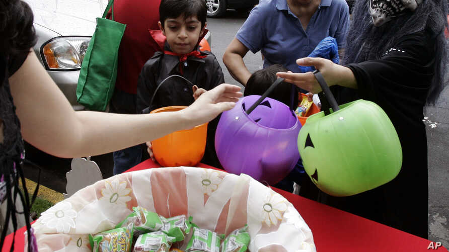 """FILE - Children wearing Halloween masks receiving candies and sweets during the """"Trick or Treat"""" tradition."""