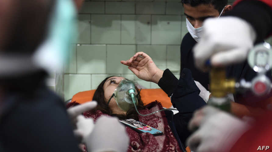 """A Syrian woman receives treatment at a hospital in the regime controlled Aleppo on Nov. 24, 2018. Official Syrian media accused the armed opposition of launching an attack with """"toxic gas"""" on the northern city."""