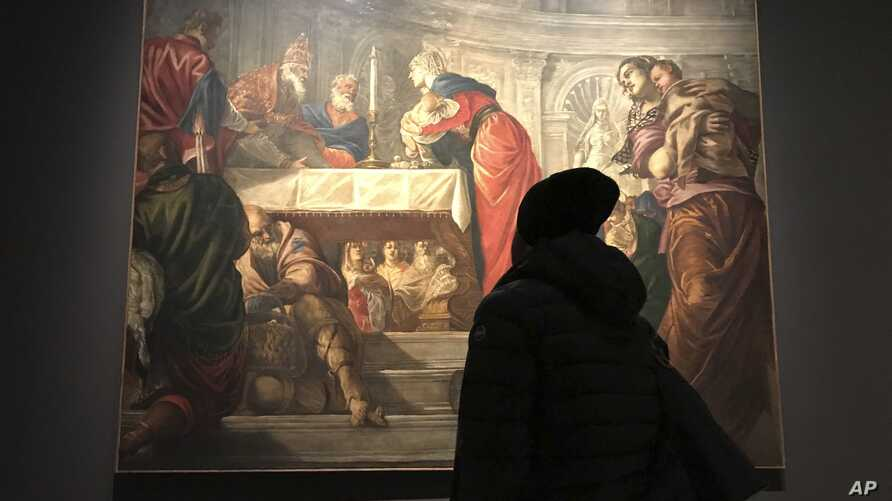 """A visitor to an exhibition of Tintoretto works looks at his """"Presentation of Jesus in the Temple"""" at the Ducal Palace in Venice, Dec. 3, 2018. After the show closes in January, it moves to the National Gallery of Art in Washington in what would be th"""