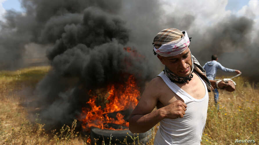 A Palestinian runs during clashes with Israeli troops, during a tent city protest along the Israel border with Gaza, demanding the right to return to their homeland, in the southern Gaza Strip, March 30, 2018.