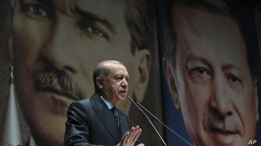 Backdropped by pictures of himself (R) and modern Turkey's founder Mustafa Kemal Ataturk (L),Turkey's President Recep Tayyip Erdogan addresses officials of his ruling Justice and Development Party (AKP), in Ankara, Turkey, Sept. 14, 2018.