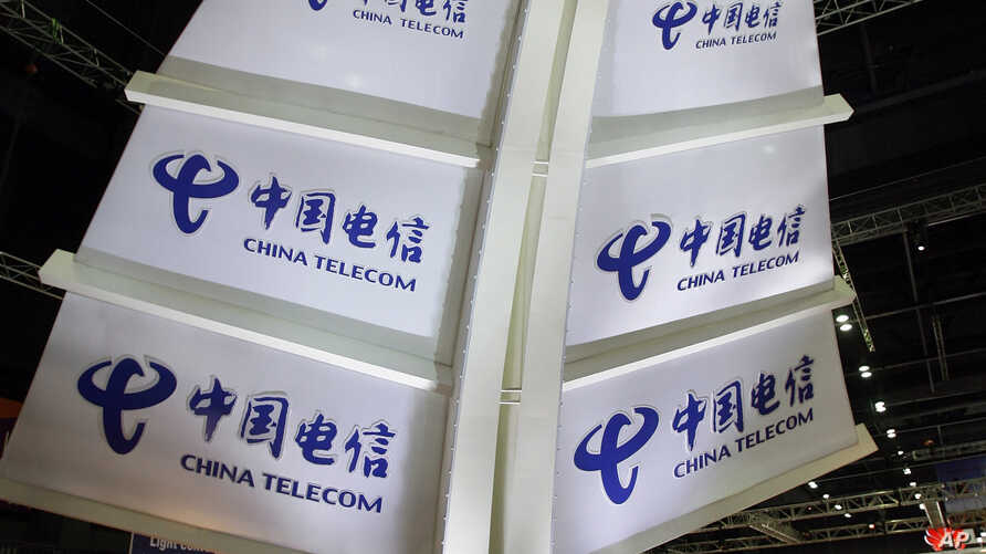 FILE - A woman walks past a China Telecom's booth during the third day of the International Telecommunication Union (ITU) Telecom World 2006 in Hong Kong, Dec. 6, 2006.