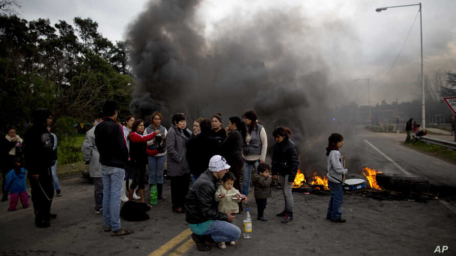 People whose homes were flooded after heavy rain protest with a burning road block in Lujan, Argentina, Aug. 11, 2015.