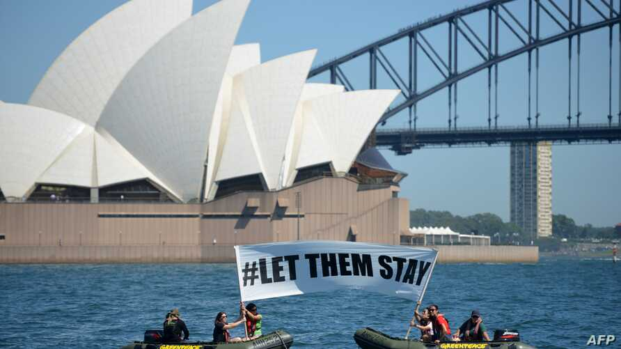 """Members of the environmental group Greenpeace hold up a sign that reads """"#LET THEM STAY"""" in front of the Opera House in Sydney, Australia, Feb. 14, 2016."""