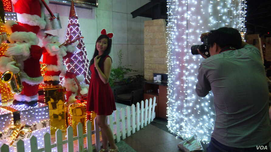 Shoppers take photos in front of Christmas decorations at a mall in Ho Chi Minh City.