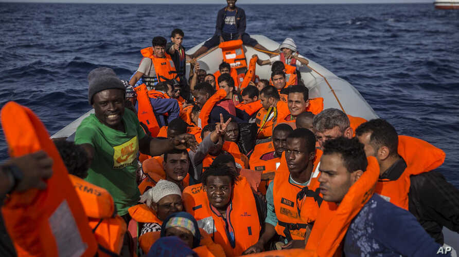 Migrants aboard a rubber dinghy off the Libyan coast are provided of life vests by rescuers aboard the Open Arms aid boat, of the Proactiva Open Arms Spanish NGO, June 30, 2018. The migrants were rescued as Italy's right-wing Interior Minister Matteo