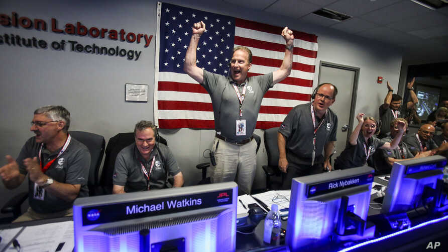 From left to right, Geoffrey Yoder, Michael Watkins, Rick Nybakken, Richard Cook and Jan Chodas celebrate in Mission Control at NASA's Jet Propulsion Laboratory as the solar-powered Juno spacecraft goes into orbit around Jupiter on Monday, July 4, 20