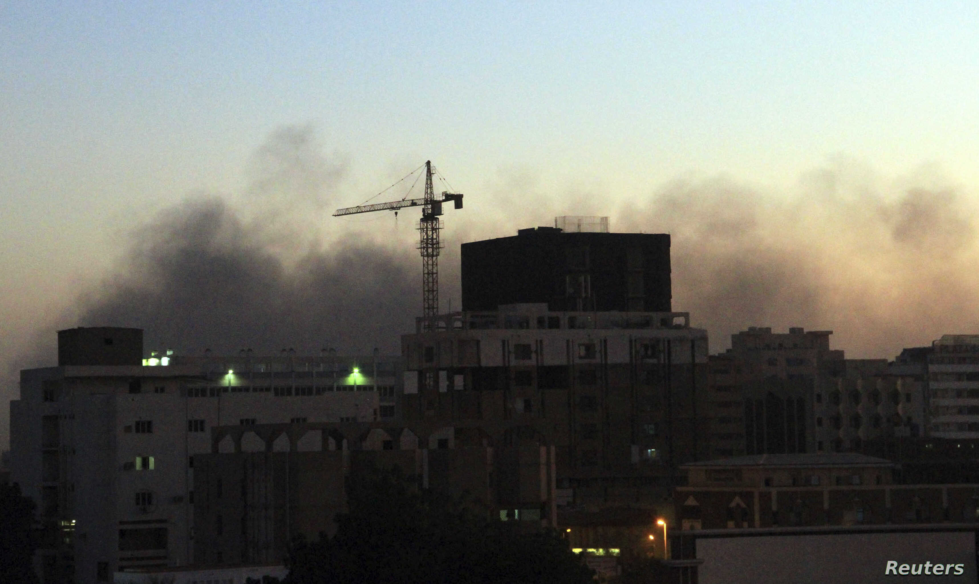Smoke rises over central Khartoum as cars burn during demonstrations over the deaths of four students from war-torn Darfur, Dec. 9, 2012.