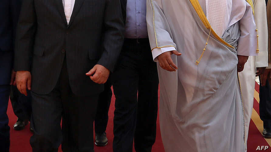 A handout photo released by the Kuwaiti news agency KUNA shows Kuwaiti Foreign Minister Sheikh Sabah al-Khaled al-Sabah (R) receiving his Iranian counterpart Mohammad Javad Zarif following his arrival at Kuwait international airport in Kuwait City on