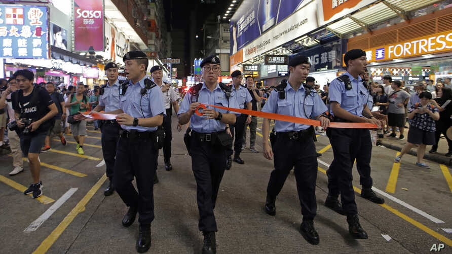 Police officers instruct street entertainers and spectators to leave on the last day before the Mong Kok's pedestrian zone closure in Hong Kong, July 29, 2018.