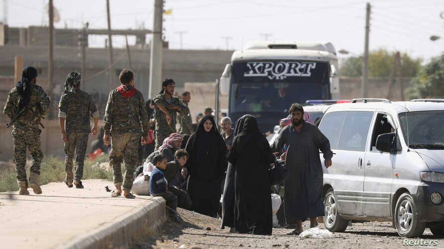 People gather along a road as they flee Raqqa, Syria, Oct. 16, 2017.