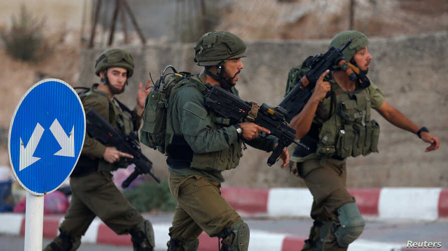 Israeli soldiers run near the scene where a Palestinian, who according to the Israeli military attempted to stab a soldier, was shot dead in Hebron in the occupied West Bank, Sept. 3, 2018.