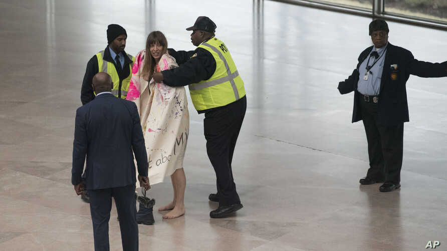 National Gallery of Art security cover Radical Matriarchy member Laura Newman with a blanket after she removed her clothes and sang during a protest in the museum, Feb. 14, 2019 in Washington.