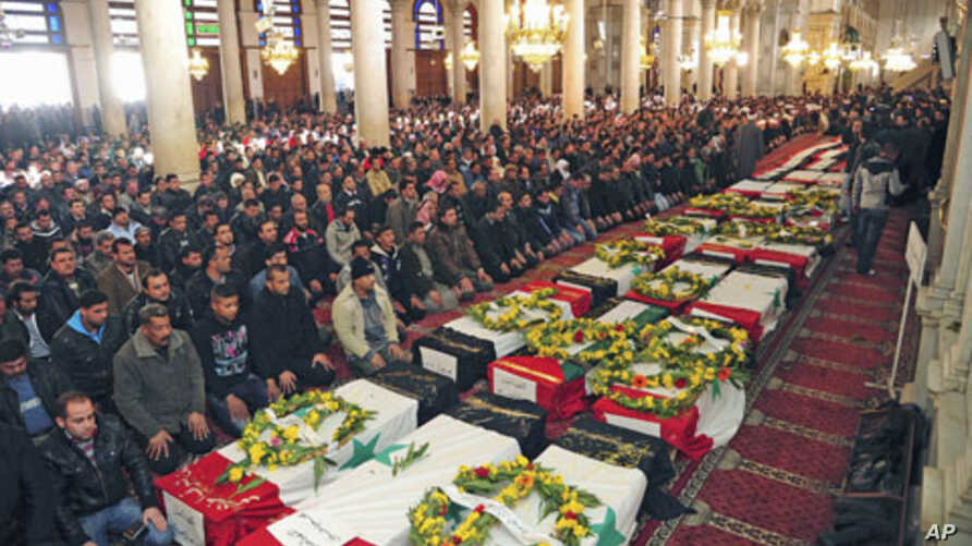 Men pray next to the coffins of people killed at security sites on Friday in two car bomb attacks, at the Umayyad Mosque in Damascus, Syria, December 24, 2011.