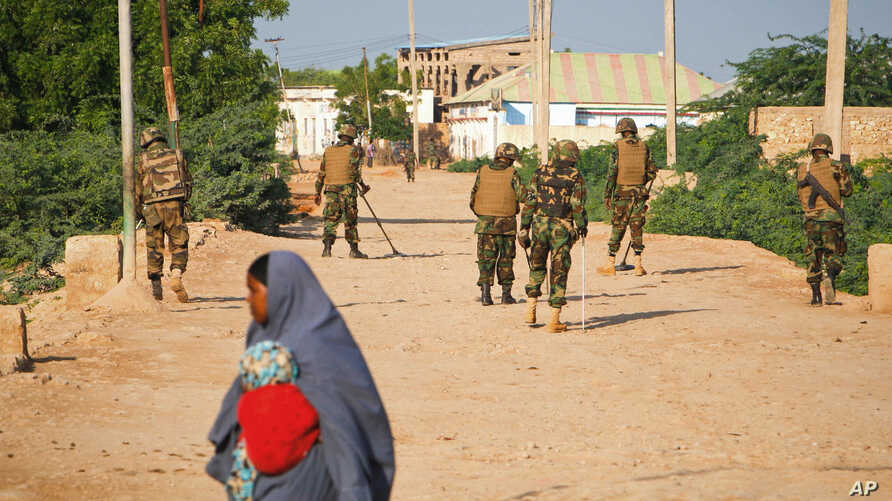 FILE - A Somali woman crosses a street while soldiers with the African Union Mission in Somalia (AMISOM) stand guard 300 kilometers west of the capital Mogadishu, on a street in Belet Weyne, Somalia. (AP)