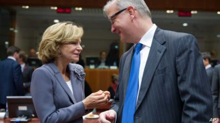 Spain's Finance Minister Elena Salgado, left, talks with European Commissioner for the Economy Olli Rehn at the start of an EU Finance Ministers meeting at the EU Council in Brussels, November 8, 2011.