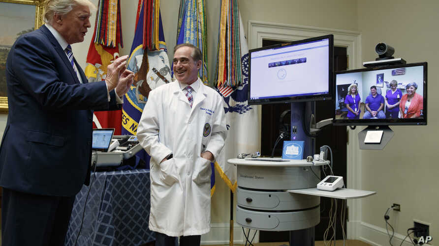 """Veterans Affairs Secretary David Shulkin watches as President Donald Trump talks with a patient during a Veterans Affairs Department """"telehealth"""" event in the Roosevelt Room of the White House in Washington, Aug. 3, 2017."""