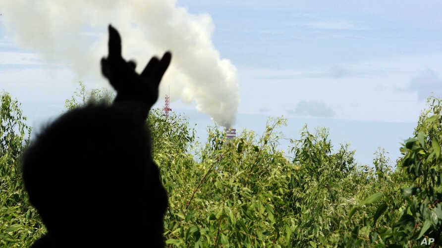 FILE - In this photo taken June 24, 2010, a fruit farmer points to a factory's chimney that blowing smoke from behind a backyard of his home near Map Ta Phut industrial estate in Rayong province, southeastern Thailand.