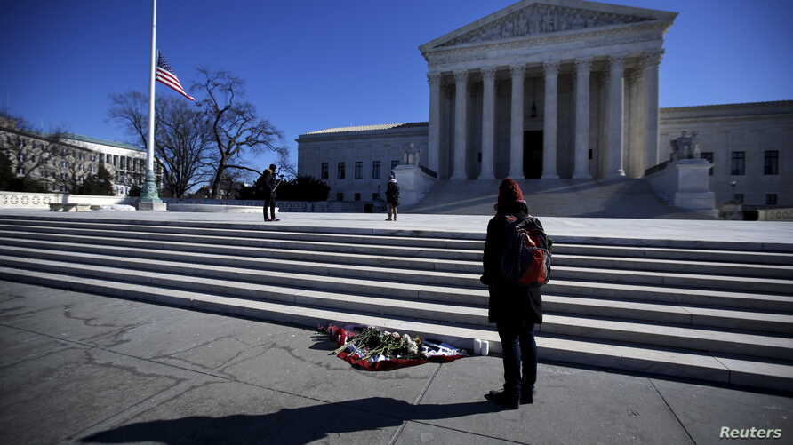 Flowers are seen as a woman stands in front of the Supreme Court building in Washington D.C. after the death of U.S. Supreme Court Justice Antonin Scalia, Febr. 14, 2016.