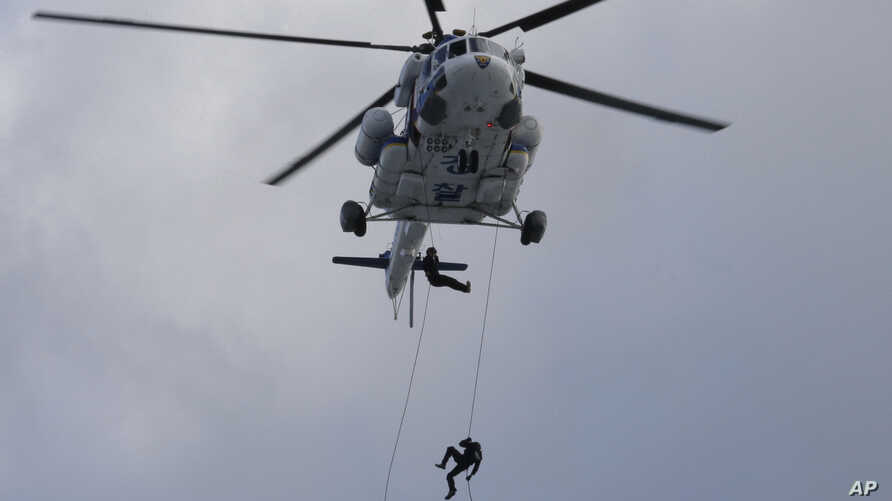 FILE - South Korean police officers rappel down from a helicopter during an anti-terror drill as part of Ulchi Freedom Guardian exercise, in Goyang, South Korea, Aug. 21, 2017.
