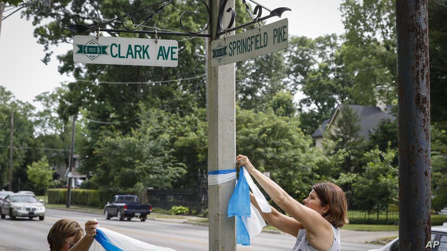 FILE - Denise Koesterman, right, and Alison Lebrun, left, tie blue-and-white awareness ribbons along Springfield Pike near the family home of Otto Warmbier, a 22-year-old University of Virginia undergraduate student who was imprisoned in North Korea.