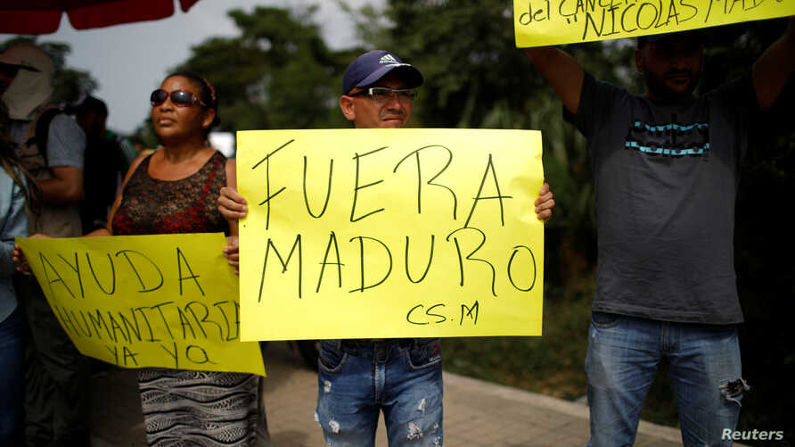 People hold placards as they wait for the arrival of trucks with international humanitarian aid for Venezuela, outside a warehouse where it will be stored according to authorities, near the Tienditas cross-border bridge between Colombia and Venezuela