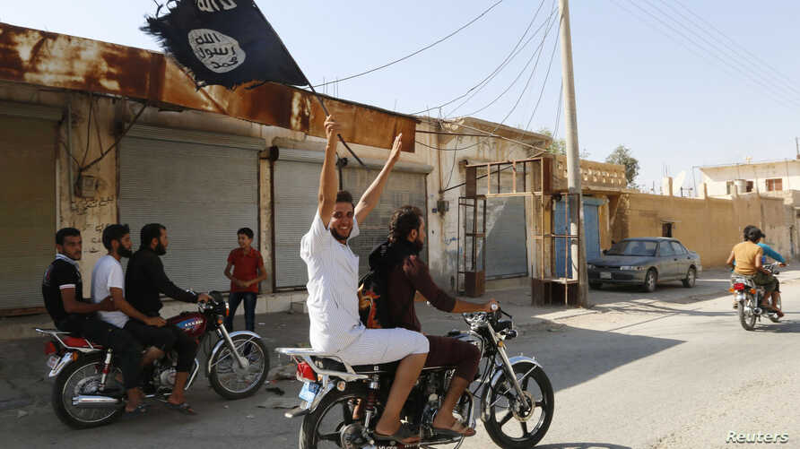 A resident of Tabqa city touring the streets on a motorcycle waves an Islamist flag in celebration after Islamic State militants took over Tabqa air base, in nearby Raqqa city, Aug. 24, 2014.