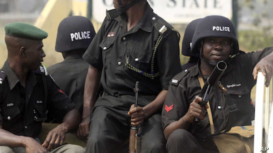 Police watch as people protest after the government suddenly removing subsidies on gasoline prices in Abeokuta, Nigeria, January 5, 2012.